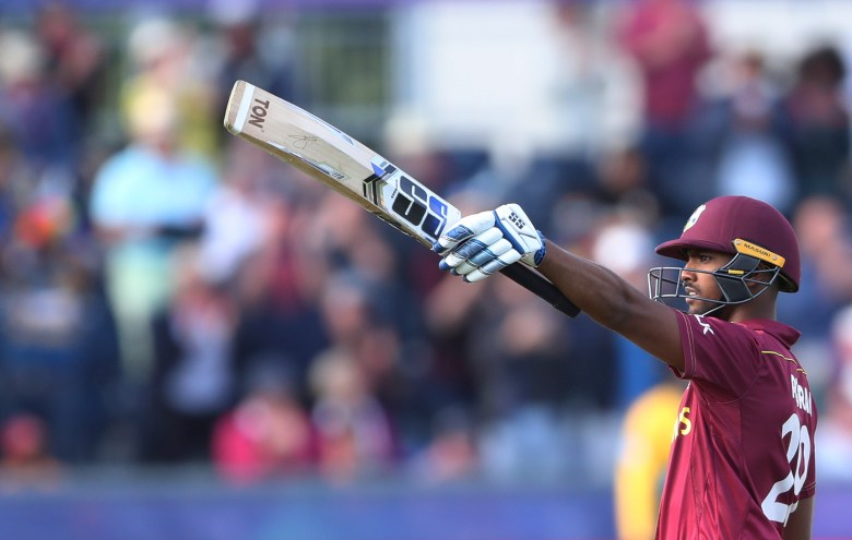 West Indies' batsman Nicholas Pooran raises his bat to celebrate scoring a century