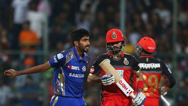 Mumbai Indians' Jasprit Bumrah, left, reacts after a shot played by Royal Challengers Bangalore batsman Manan Vohra