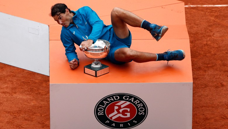 Spain's Rafael Nadal jokes with the cup on the podium after defeating Austria's Dominic Thiem in the men's final match of the French Open tennis tournament at the Roland Garros stadium