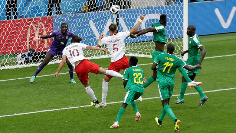 Poland's Grzegorz Krychowiak, left, scores his side's first goal during the group H match between Poland and Senegal at the 2018 soccer World Cup in the Spartak Stadium in Moscow