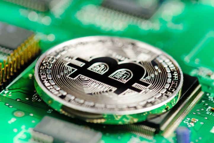 82774067 - silver bitcoin virtual currency on a circuit board background