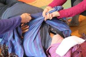 Angie et Chantal serrent le rebozo au niveau du thorax, le maintiennent un certain temps avant de relacher la tension et replacer le rebozo.