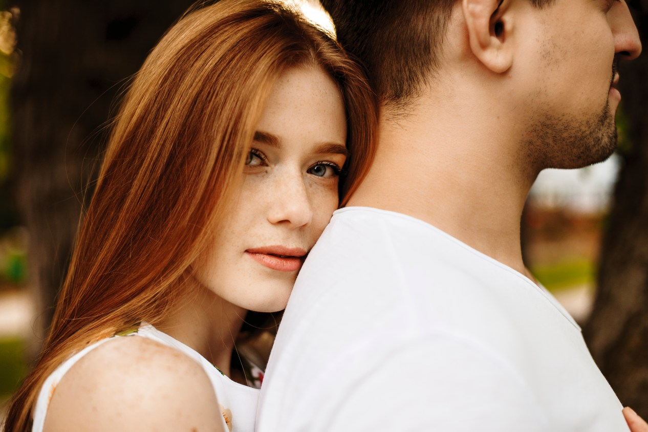 A red-haired woman rests her head on the back of a brown-haired man while she looks at the camera.