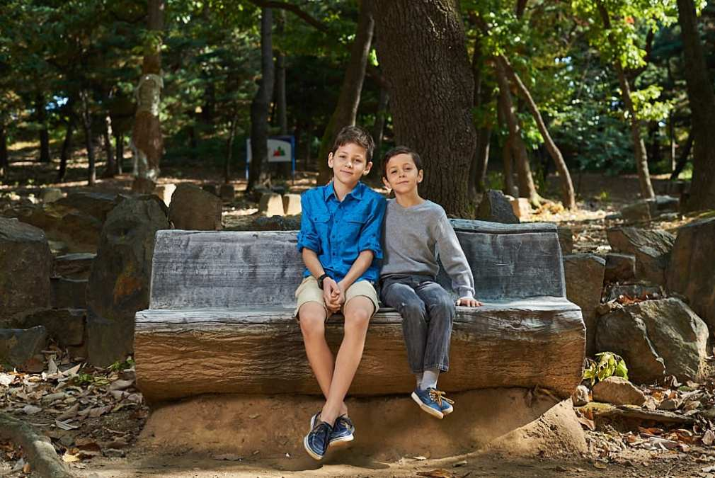 Brothers sitting on a bench in a park