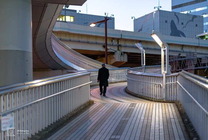 Man walking during the evening time on one of the many pedestrian overpasses available in Yokohama Photography by Cristian Bucur, Photographer in Tokyo.