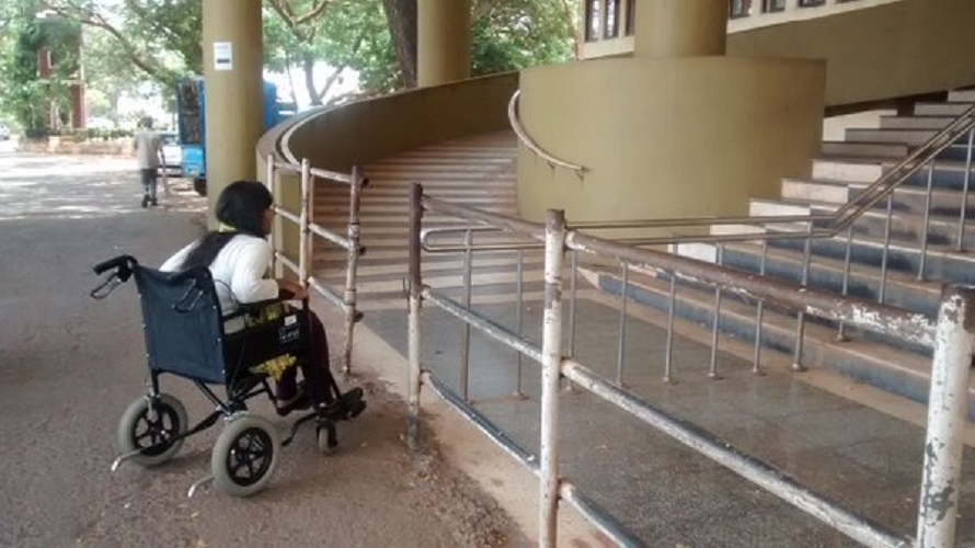 photo of woman in wheelchair facing difficulty going up stairs