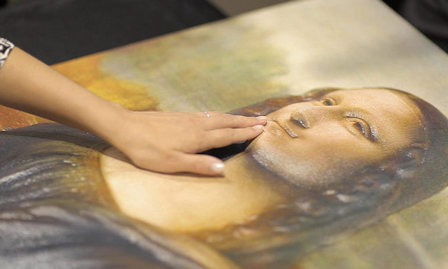 woman's hand touching a relief photo of the mona lisa