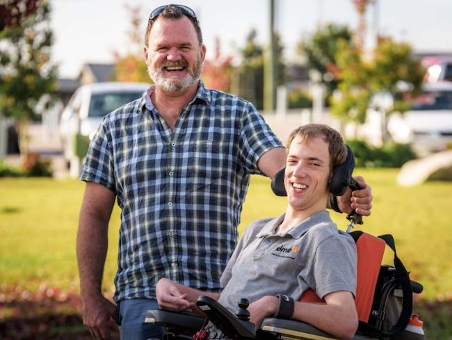 photo of two men. one is standing, the other in a wheelchair