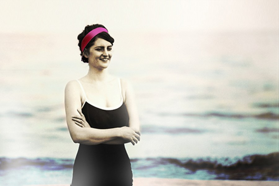 Woman in vintage early 20th century swimmers stands with arms crossed with her feet in the ocean.