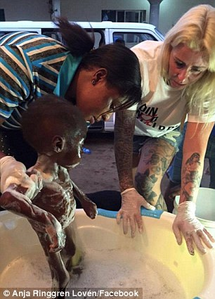 Ms Loven is pictured helping give Hope a bath after he was found walking the streets starving, disorientated and riddled with worms