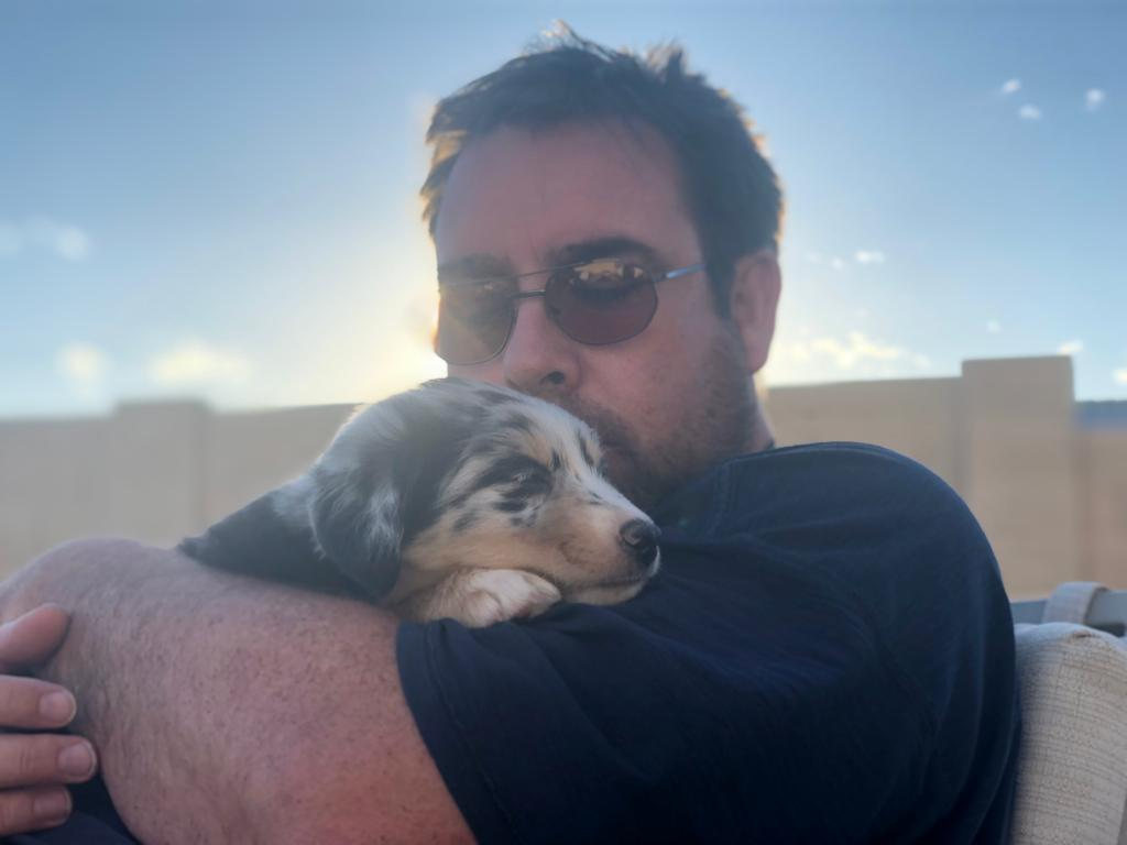 tony and river cuddle austrailian shepherd Critter Caretakers Pet Services Tony Bacon Owner of Critter Caretakers