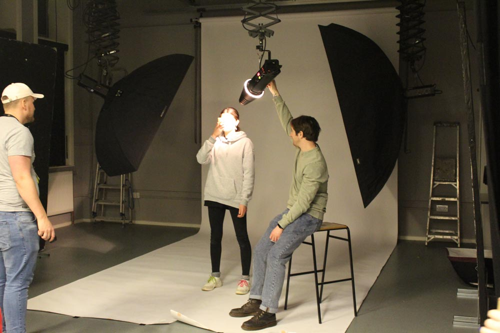 Student setting up photography studio equipment