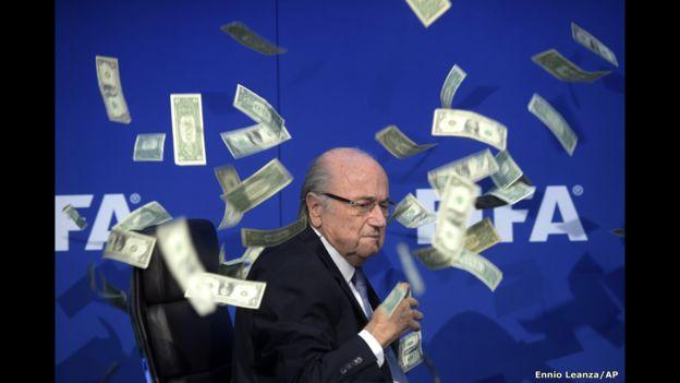 El presidente de la FIFA, Sepp Blatter, yace en su asiento mientras caen los billetes lanzados por el comediante británico Simon Brodkin. La imagen fue reflejo del año de escándalos que afectó a la FIFA y que terminó con la suspensión por ocho años de Blatter y el francés Michel Platini.