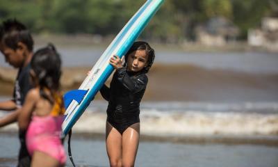 Dayana, de 9 años, carga su tabla durante una clase gratis de surf, el 14 de septiembre de 2020 en Iztapa, Guatemala