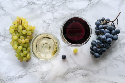 Red and white wine and grapes in glass on marble.