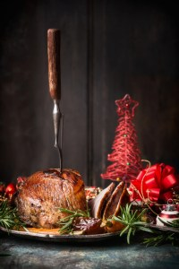 Roasted sliced Christmas ham with fork and red festive holiday decoration at dark wooden background.