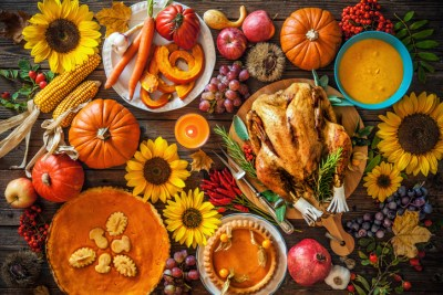 Thanksgiving dinner. Roasted turkey with pumpkins and sunflowers on wooden table.
