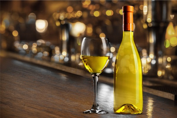 White wine bottle and glass on bar and background.