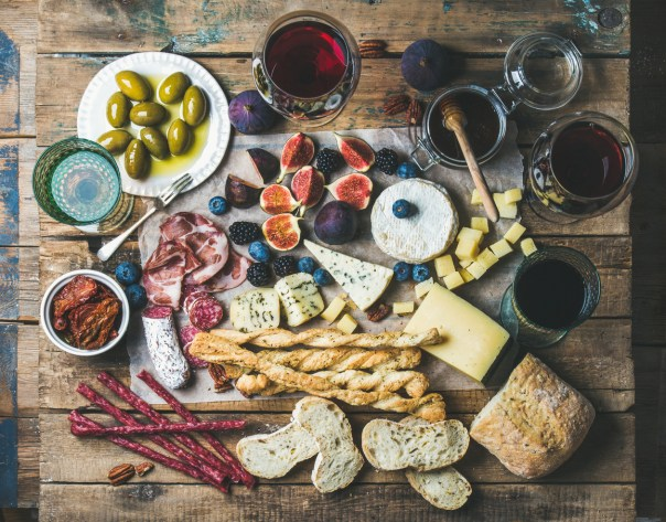 Wine and snack set with various wines in glasses, meat variety, bread, sun-dried tomatoes, honey, green olives, figs, nuts and berries on wax paper over rustic wooden table background, top view