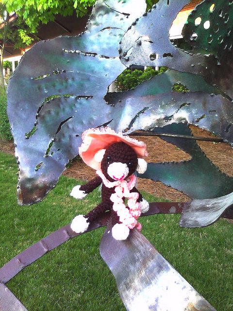 Close up of Georgina the crochet monkey surveying a sculpture