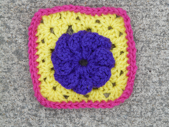A crochet square with a crochet flower at its center