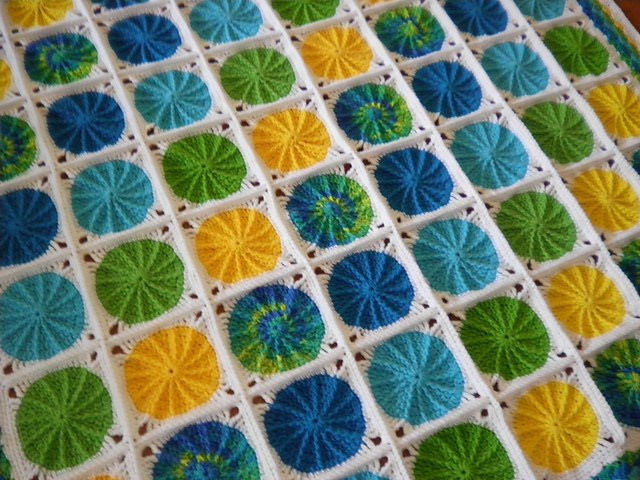 A textured circle afghan made of greens yellows, and blues