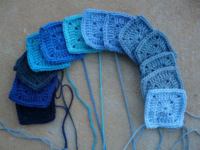 A rainbow of thirteen blue crochet squares