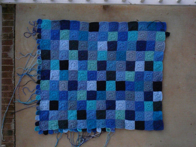 A crochet blanket made from crochet squares worked in many blue shades of yarn