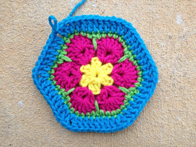 An African flower crochet hexagon with a blue border