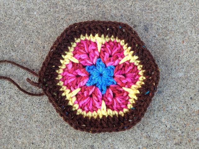an African flower crochet hexagon with a brown fleck border