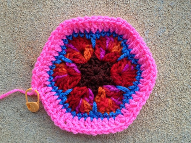 An African flower crochet hexagon with a bright pink border