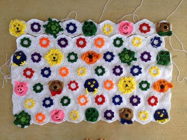 the first seven rows of textured crochet flower hexagons and an assortment animal crochet hexagons