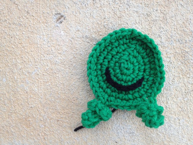 The green crochet frog that went misssing frolicking on the front porch