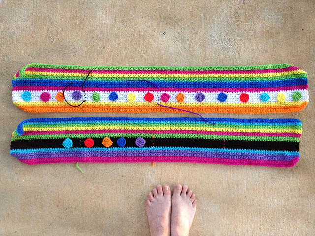 two crochet stripe strips decorated with small crochet squares