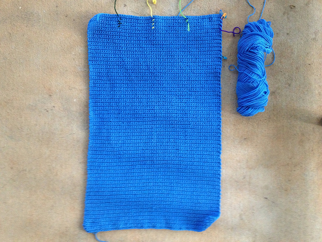 the blue center panel of a crochet blanket worked in single crochet stitches