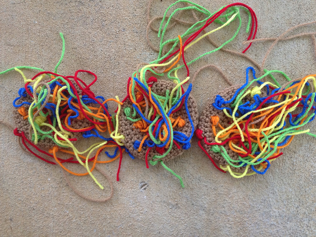 Three large multi-color candy crochet cookies with ends in need of weaving in