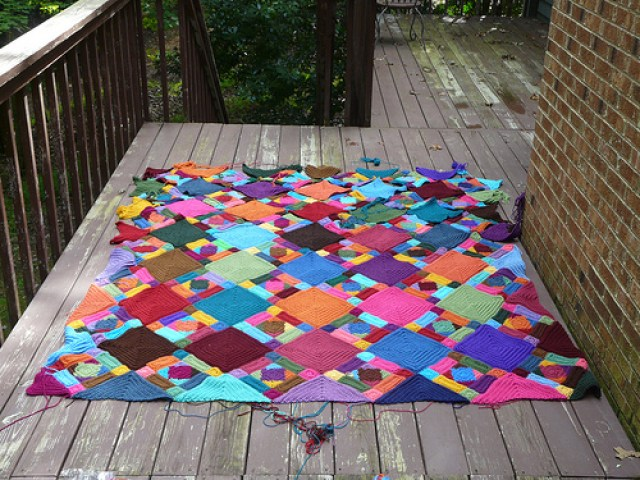 A crochet afghan made from textured crochet squares, textured crochet rectangles, and textured crochet triangles