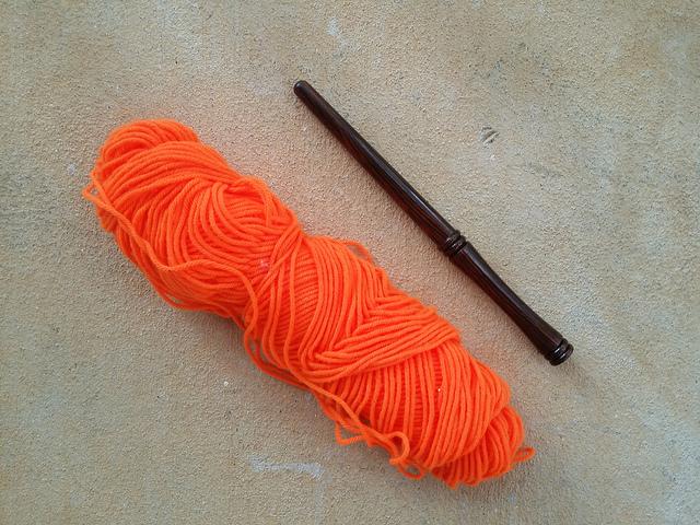 orange yarn and a nostepinne