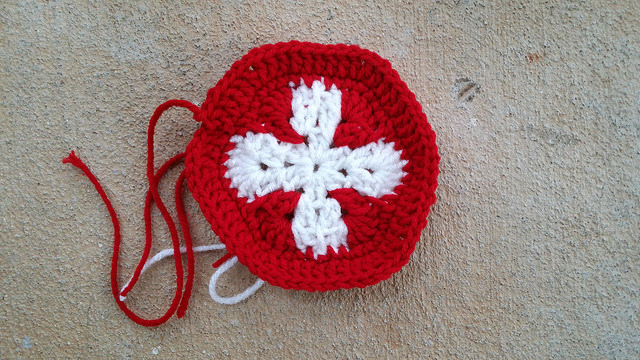 A crochet hexagon inspired by the flag of Switzerland that I finished despite running errands and more errands
