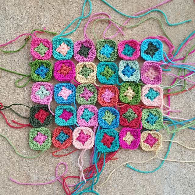 Thirty two-round granny squares made in an afternoon of plein air crochet