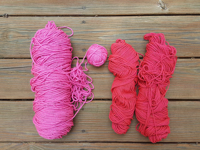 partial skeins of red and pink yarns in my yarn stash