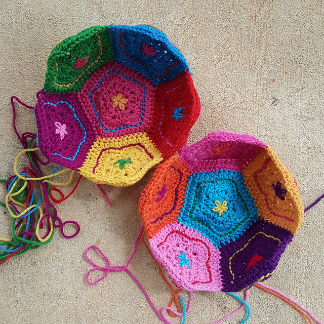 two half of a multicolor crochet dodecahedron ready to be joined