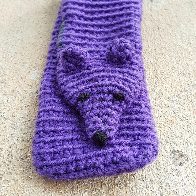 purple crochet mink with two crochet ears and an embroidered face
