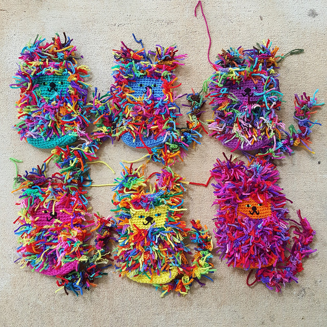 Six scrap yarn crochet cats to-be that are all done but the stuffing