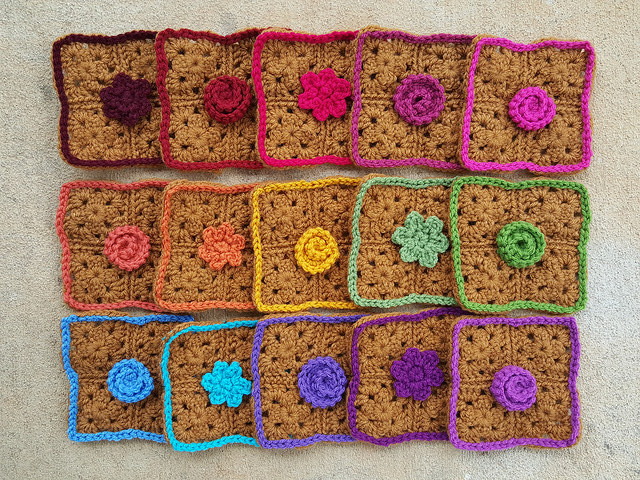 fifteen four-patch granny squares decorated with crochet flowers