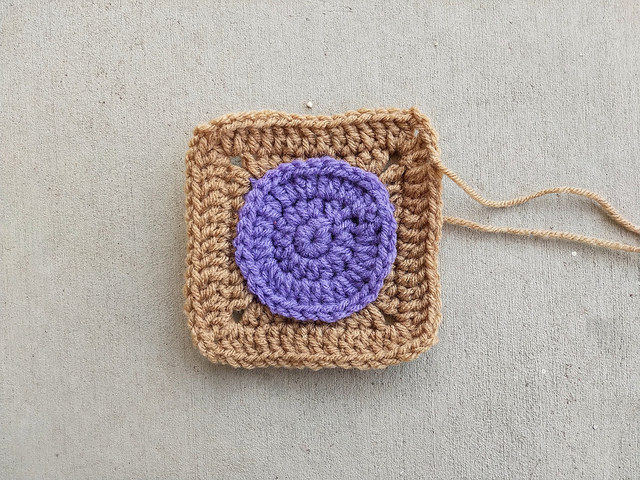 a crochet square with a lavender crochet circle at the center