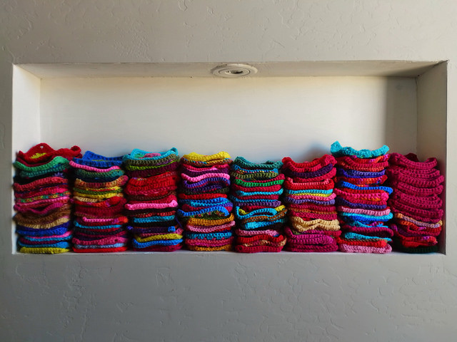 Lots of crochet squares stacked in a nook in the wall