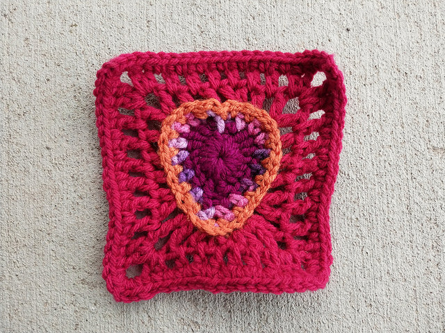A crochet square with a boho crochet heart at the center