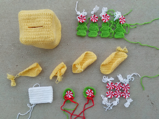 The pieces of a yellow Gingerbread House tissue box crochet cozy