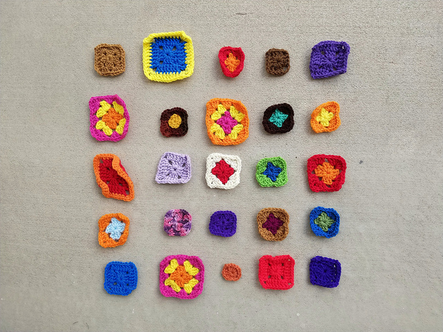 Twenty-five granny square remnants ready for the first round of crochet rehab